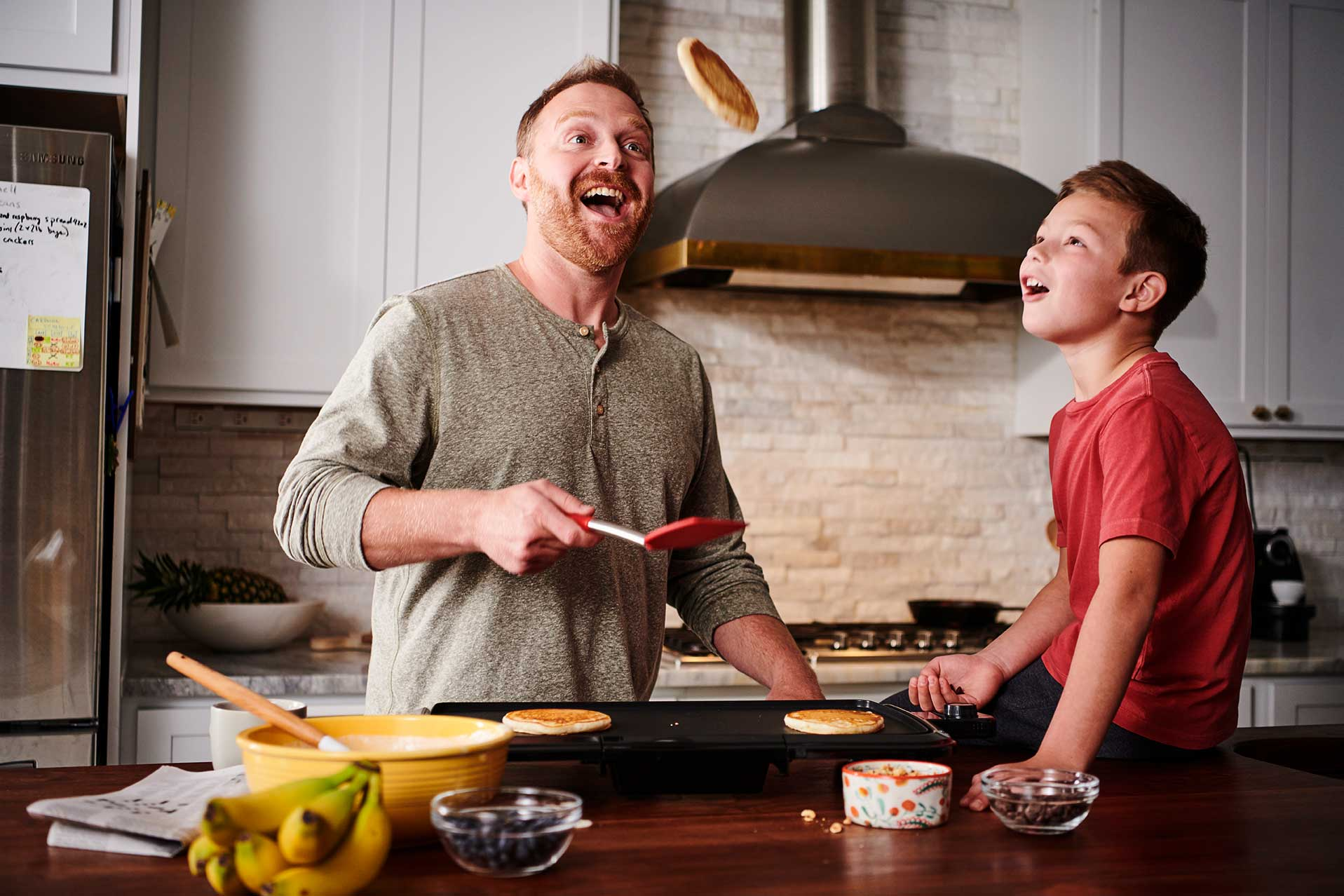 A father flips a pancake while his son watches with awe.